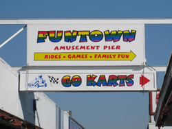 a boardwalk sign advertising for the Funtown Pier